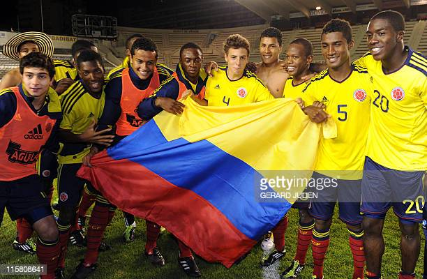 Colombia's players celebrate with the Colombian national flag after winning the Under 21 International tournament final football match France vs...