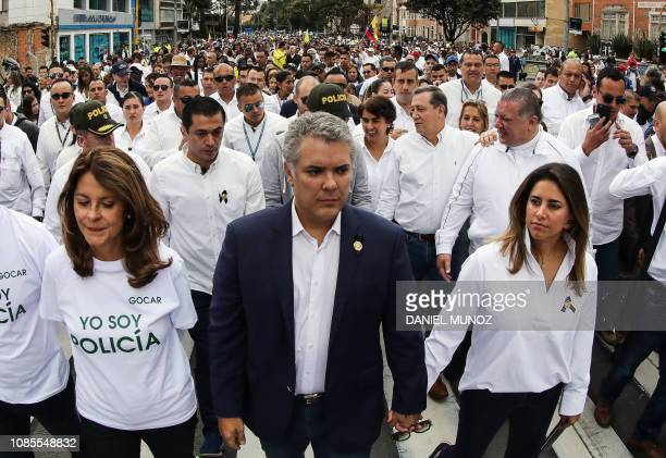 Colombia's President Ivan Duque flanked by his wife Maria Juliana Ruiz and Colombian Vice President Marta Lucia Ramirez takes part in a march against...