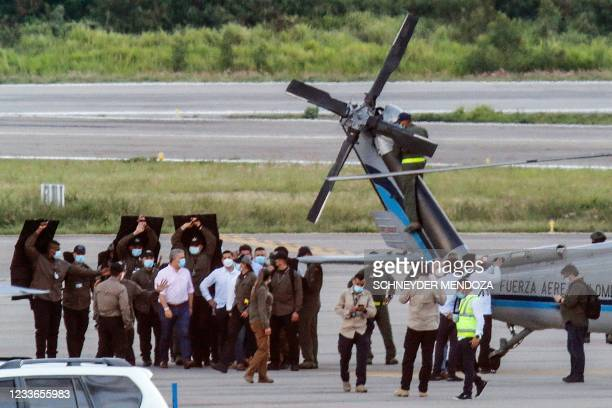 Colombia's President Ivan Duque walks surrounded by bodyguards close to the presidential helicopter at the tarmac of the Camilo Daza International...