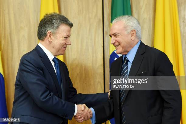 Colombia's President Juan Manuel Santos and Brazilian President Michel Temer shake hands after signing agreements during a ceremony at Planalto...
