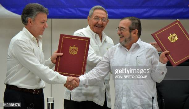 TOPSHOT Colombia's President Juan Manuel Santos and Timoleon Jimenez aka Timochenko head of the FARC leftist guerrilla shake hands accompanied by...