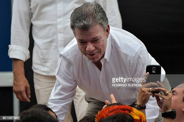 Colombia's President Juan Manuel Santos greets people during the signing ceremony of an agreement that finally delineates the maritime boundary...