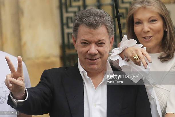 Colombia's President Juan Manuel Santos makes the victory/peace sign with wife Maria Clemencia Rodriguez after voting in the referendum on a peace...