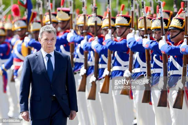 Colombia's President Juan Manuel Santos reviews the honour guard during his welcoming ceremony at Planalto Palace in Brasilia where he will meet his...