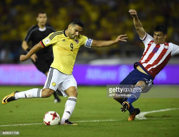 Colombia's Radamel Falcao and Paraguay's Fabian Balbuena vie for the ball during their 2018 World Cup football qualifier match in Barranquilla...