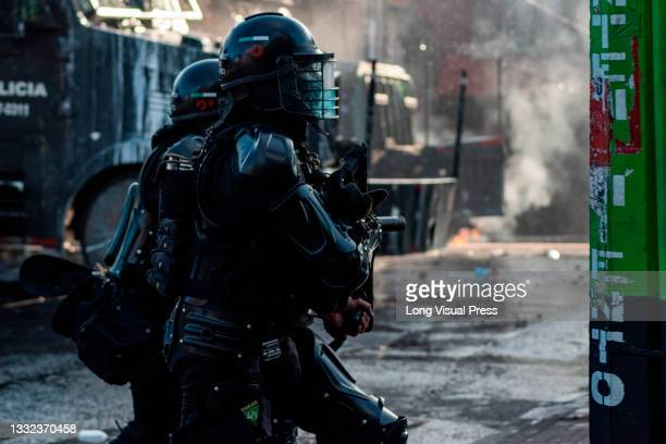 Colombia's riot police officers stand as demonstrators prepare to clash as demonstrations ended in late-night clashes between riot police and...