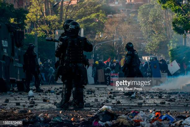 Colombia's riot police officers stand in the middle of a street with rocks and debree thrown by demonstrators as demonstrations ended in late-night...