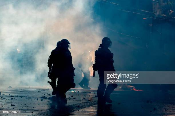 Colombia's riot police officers stand in the middle of a tear gas cloud as demonstrations ended in late-night clashes between riot police and...