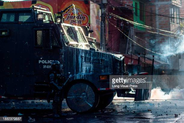 Colombia's riot police officers take cover behind a riot armored truck as demonstrations ended in late-night clashes between riot police and...
