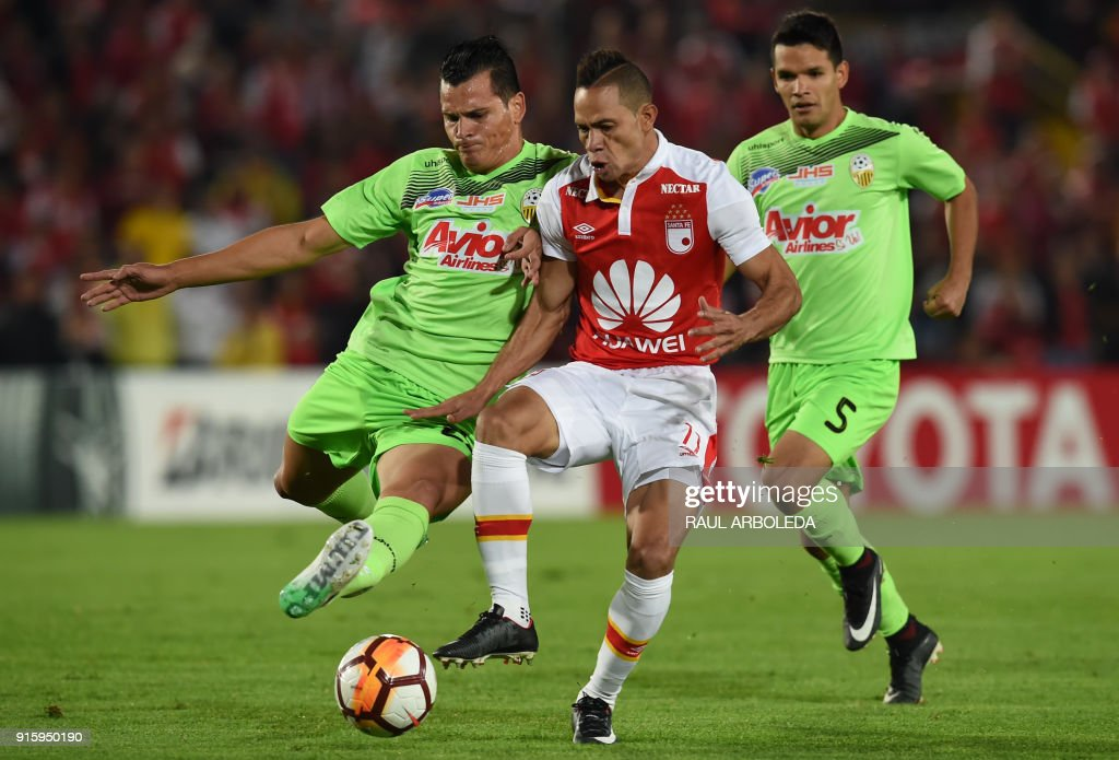 Colombia's Santa Fe player Anderson Plata (C) vies for the ball with Venezuela's Tachira player Jan Vargas (L) during their Copa Libertadores football match at Nemesio Camacho El Campin stadium in Bogota, Colombia on February 8, 2018. / AFP PHOTO / Raul ARBOLEDA