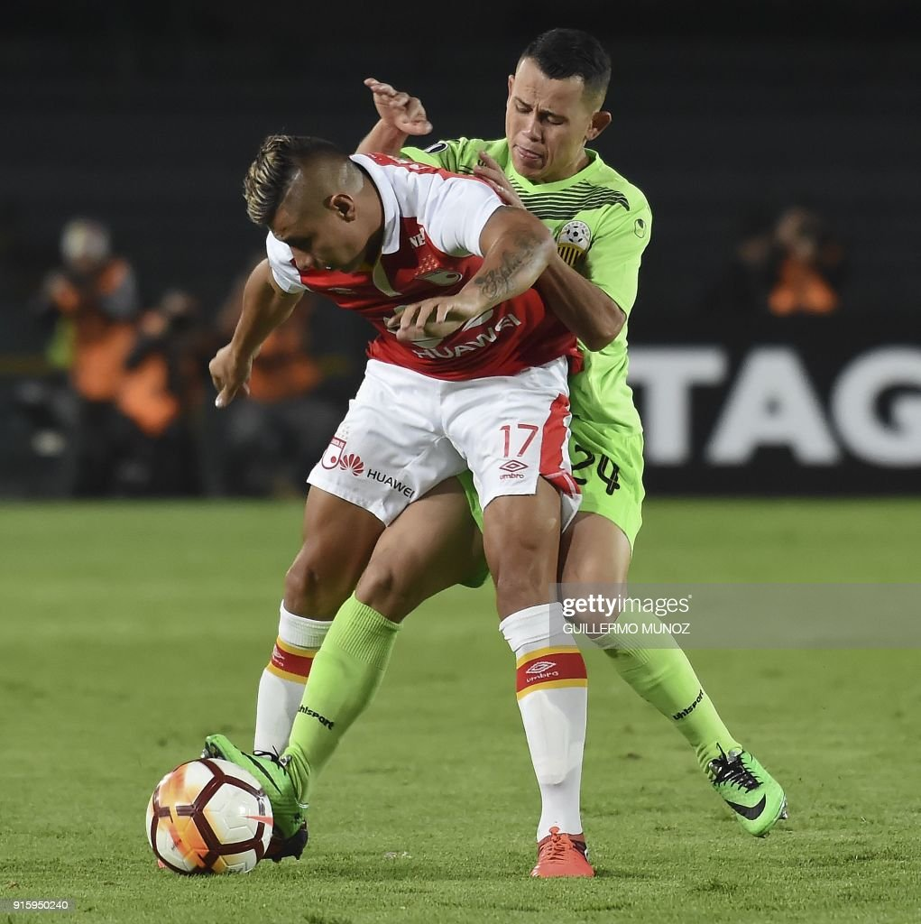 Colombia's Santa Fe player Juan Roa (back) vies for the ball with Venezuela's Tachira player Luis Chacon during their Copa Libertadores football match at the El Campin stadium in Bogota Colombia on February 8, 2018. /
