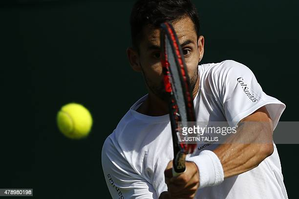 Colombia's Santiago Giraldo returns against Brazil's Joao Souza during their men's singles first round match on day one of the 2015 Wimbledon...