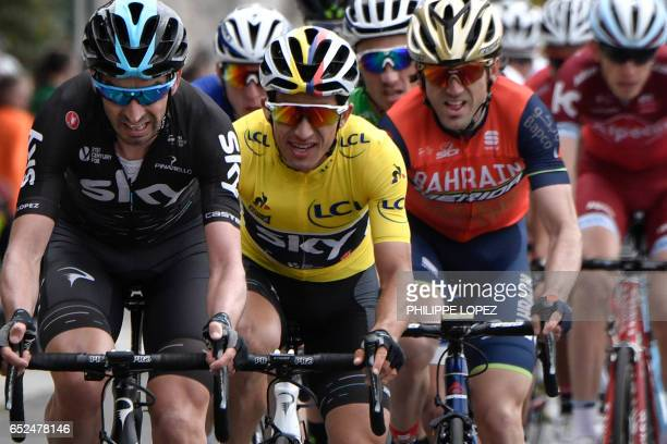Colombia's Sergio Henao wearing the overall leader's yellow jersey rides behind Spain's David Lopez during the 1155 km eighth and last stage of the...