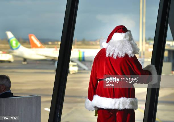 ColombierSaugnieu Lyon SaintExupery Airport Santa Claus Father Christmas looking at planes on the tarmac through the large windows of the waiting room