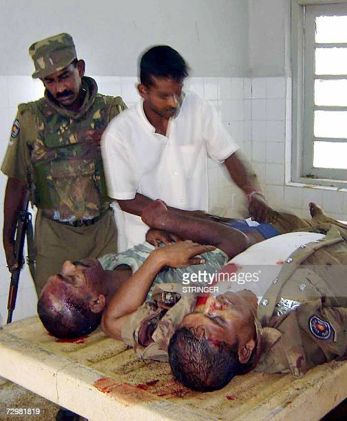 A Sri Lankan policeman and a morgue worker inspect the bodies of two constables killed 12 January 2007 in a roadside bomb attack in the northern Sri...