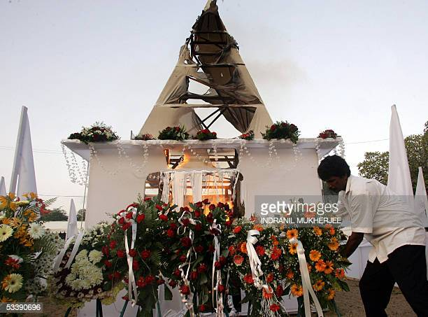 A Sri Lankan worker places flowers in front of the burning funeral pyre of slain Sri Lankan Foreign Minister Lakshman Kadirgamar in Colombo 15 August...