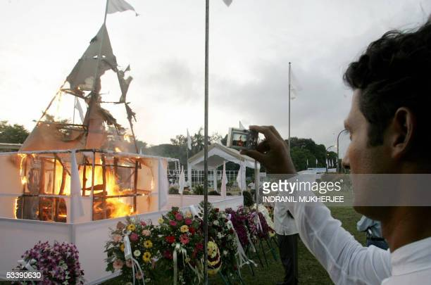 Raghavan Kadirgamar son of slain Sri Lankan Foreign Minister Lakshman Kadirgamar takes a picture of his father's burning funeral pyre after...