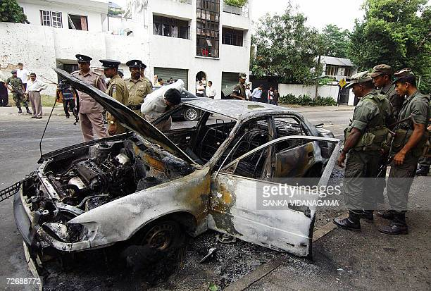 Sri Lanka army personnels watch a wrecked vehicle at the site of a suicide bomb attack on a defence ministry convoy in Colombo 01 December 2006 Sri...