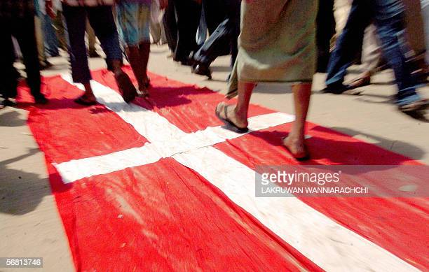 Sri Lankan Muslims walk across a Danish flag as they take part in a rally in Colombo10 February 2006 to protest cartoons in a Danish newspaper...