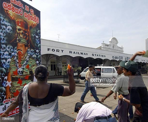 Sri Lankan pedestrians throw tomatos towards a billboard featuring an image of Liberation Tigers of Tamil Eelam Leader Velupillai Prabhakaran outside...