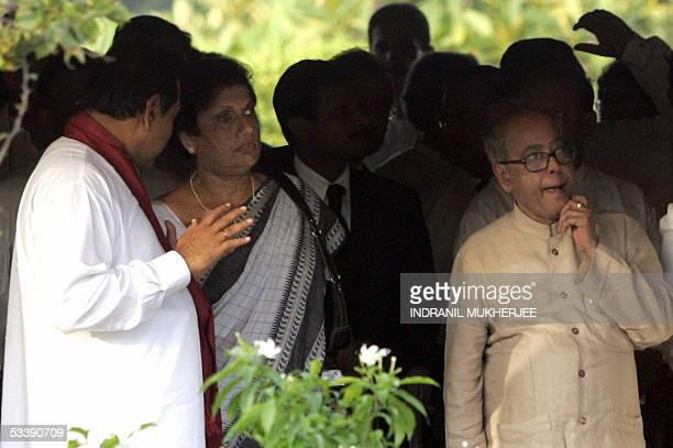 Sri Lankan Prime Minister Mahinda Rajapakse gestures as he speaks with President Chandrika Kumaratunga as they and Indian Defence Minister Pranab...