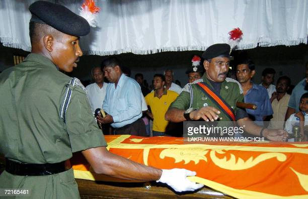Sri Lankan soldiers drape the national flag over the coffin of Army Major Sampath Thanthirige before it is taken to a Buddhist temple in Colombo 14...