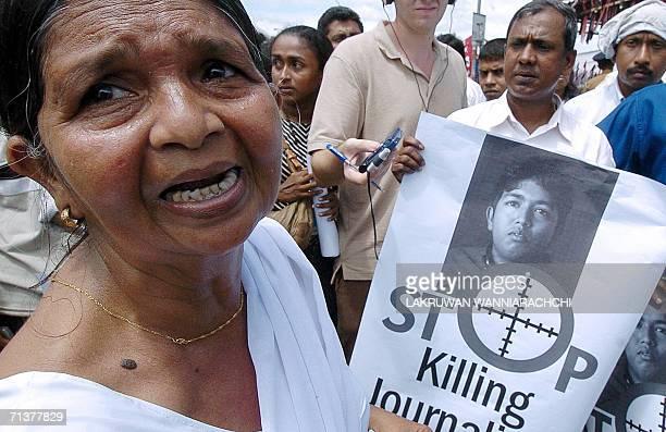 Sri Lankan woman Rupa de Silva weeps while carrying a photograph of her slain journalist son Sampath Lakmal de Silva during a protest demonstration...