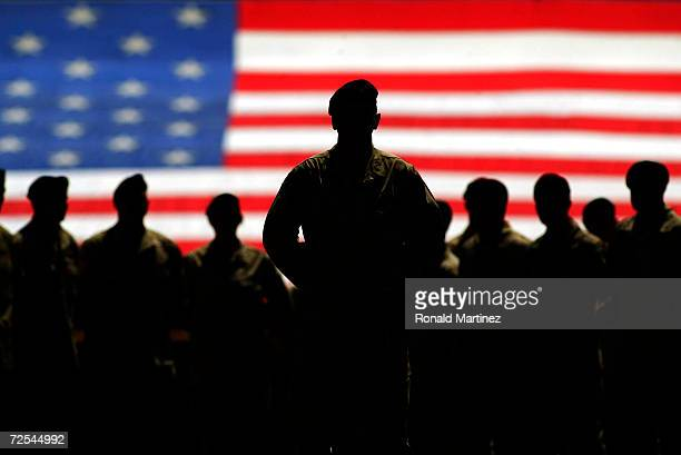Colonel Don Campbell with members of the United States Army Fourth Infantry Division stand in front of the American flag prior to the home opener...