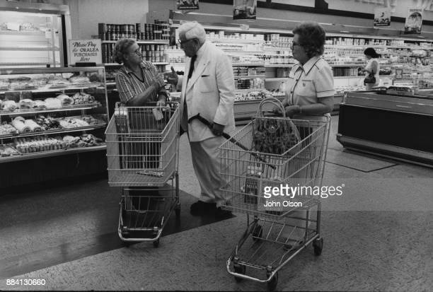 Colonel Harland David Sanders and his wife Claudia in in a supermarket speaking to unidentified woman Kentucky September 1974