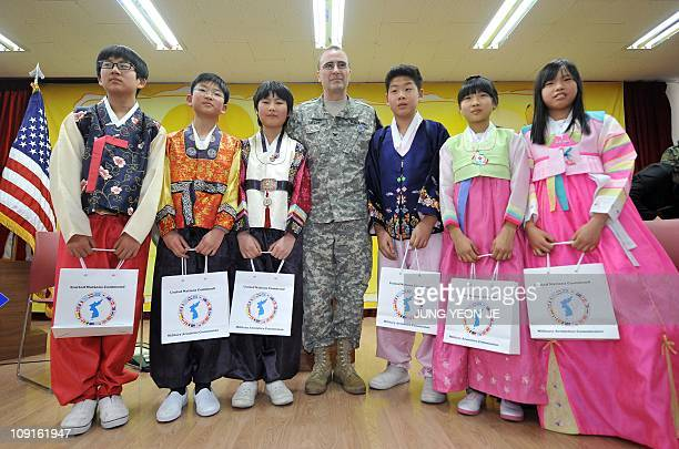 US Colonel Kurt Taylor from the United Nations Command Military Armistice Commission poses with South Korean graduates of Taesungdong Elementary...