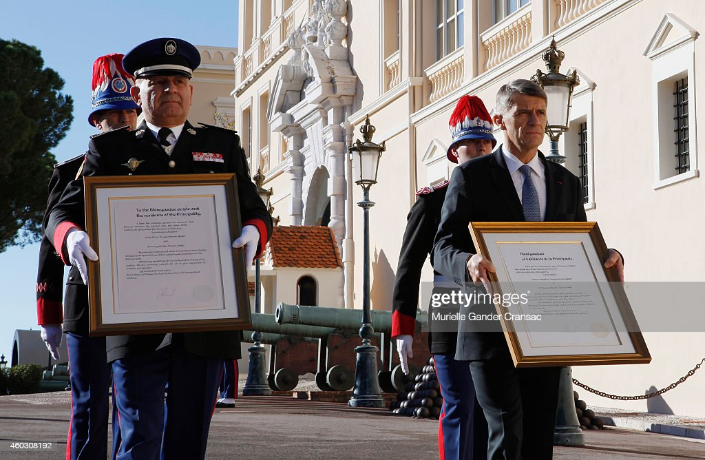 Colonel Luc Frigan (L) and Chamberlain Laurent Soler carry the official announcement of the birth of the royal twins Prince Jacques and Princess Gabriella to the outside wall of the Monaco Palace on December 11, 2014 in Monaco, Monaco.