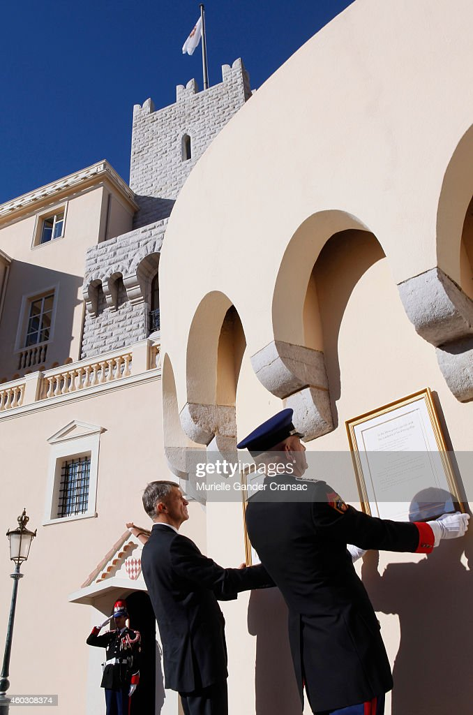 Colonel Luc Frigan (L) and Chamberlain Laurent Soler place the official announcement of the birth of the royal twins Prince Jacques and Princess Gabriella onto the outside wall of the Monaco Palace on December 11, 2014 in Monaco, Monaco.
