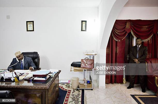Colonel Mohamed Bacar the selfproclaimed leader of the Indian Ocean island of Anjouan works in his office as one of his bodyguards keeps watch at the...