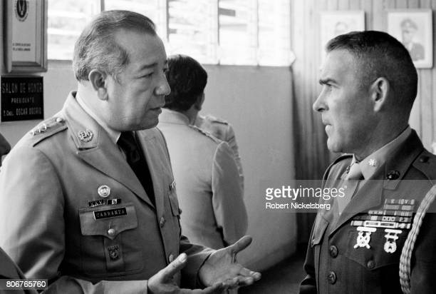 Colonel Nicolas Carranza left head of the Salvadoran treasury police speaks with Lt Col Philip Ray right the US Naval Attaché at a farewell ceremony...