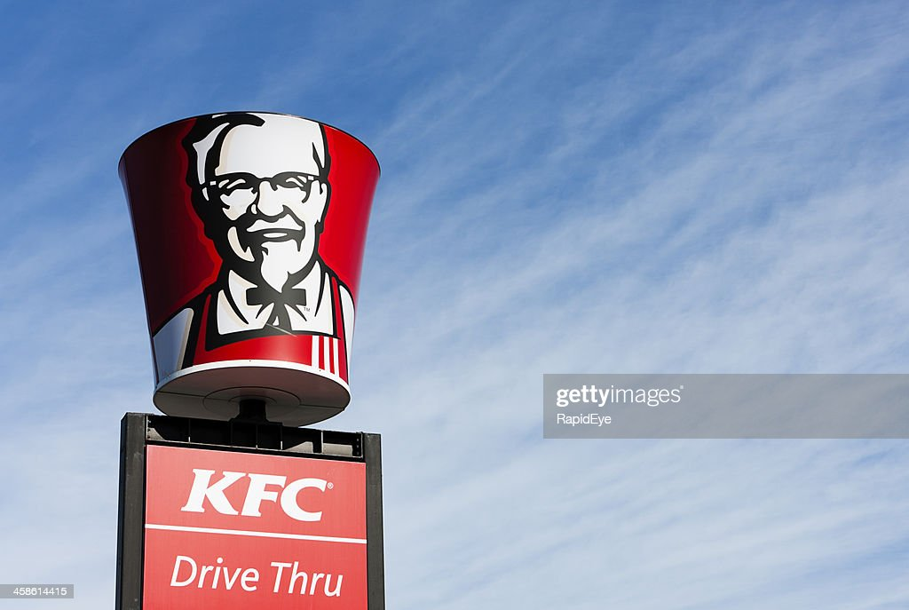Colonel Sanders' image on bucket-shaped sign above KFC franchise : Stock Photo