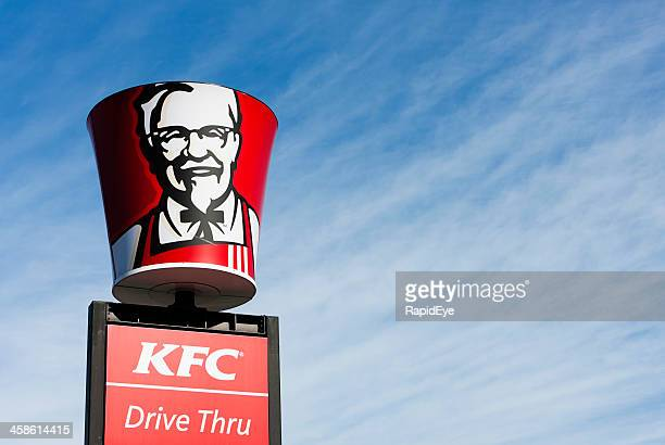 Colonel Sanders' image on bucket-shaped sign above KFC franchise