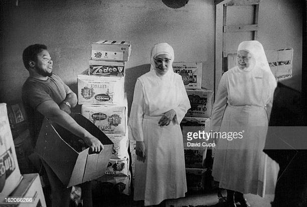 """Colonel Thorpe carries produce for Sister Louise, left, and Sister Monique, who has collected for 10 years. """"Collecting"""" is done daily by 2-member..."""