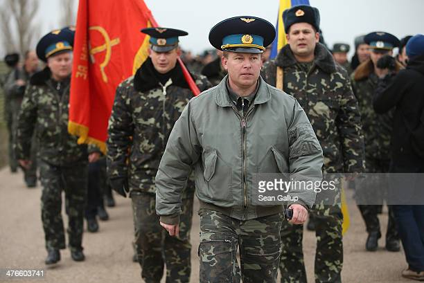 Colonel Yuli Mamchor commander of the Ukrainian military garrison at the Belbek airbase leads his unarmed troops bearing the Ukrainian and regiment...