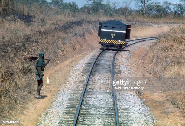 A Colonial Portuguese soldier stands beside train tracks as an armed railroad car approaches during the Mozambican War of Independence Mozambique...