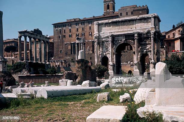 A colonnade of the Temple of Saturn lies beyond the ruined Arch of Septimus Severus erected in 203 AD