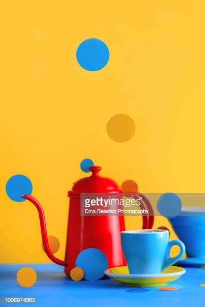 color block coffee equipment still life. kettle and porcelain coffee cups on a vibrant yellow background. geometry and color in food photography. suprematic concept with copy space - hot tea stock pictures, royalty-free photos & images
