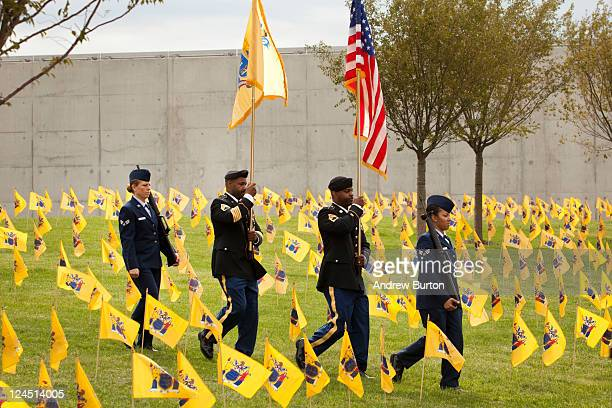 A color guard walks through New Jersey state flags during the dedication of the Empty Sky Memorial structure at Liberty State Park on September 10...