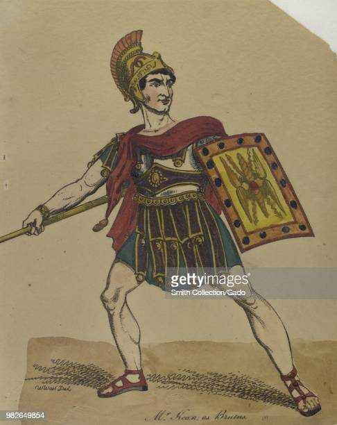 Color illustration depicting a fulllength view of British actor Edmund Kean as Brutus with a serious expression on his face holding a spear in one...