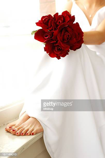 Color Image of Bride Sitting on Windowsill Holding Red Roses