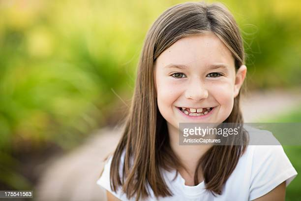 Color Image of Happy Young Girl Sitting Outdoors