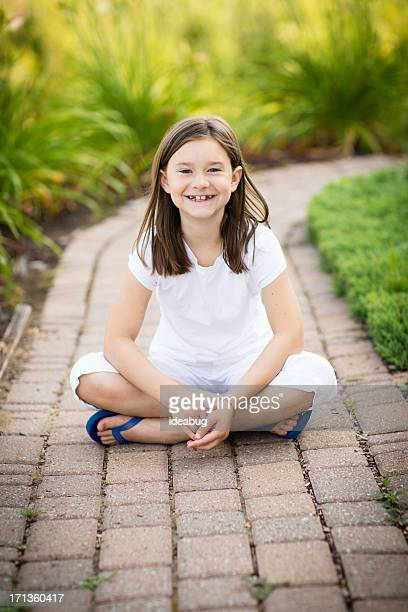 Color Image of Happy Young Girl Sitting Outsi