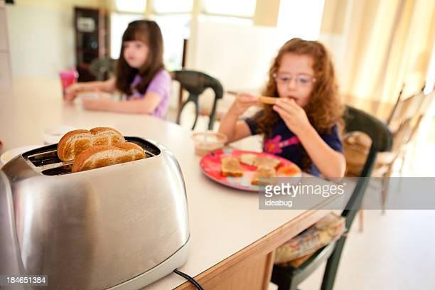Image en couleur de sœurs manger dans la cuisine à domicile