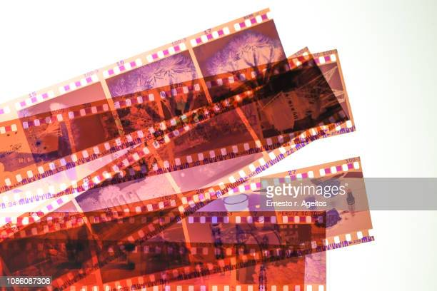 color negative 35mm film stripes stacked on a lightbox - camera film stock photos and pictures