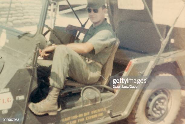 Color photograph of a male soldier in fulllength threequarter profile view wearing a uniform sunglasses and hat looking at the camera with a relaxed...