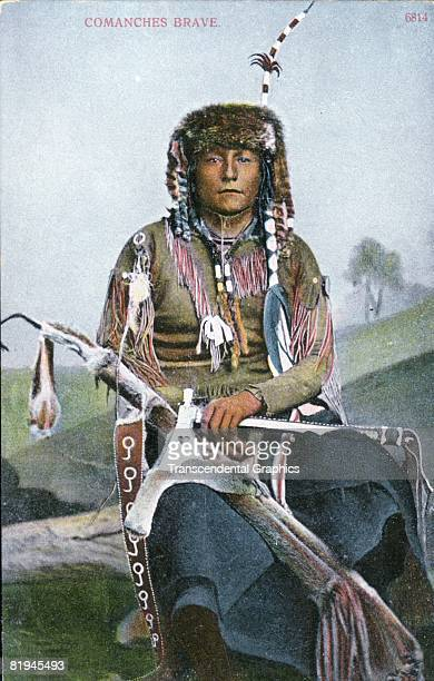 Color postcard of a Comanche brave sitting down holding his sheathed rifle and tomahawk Published by AC Bossleman Publishing